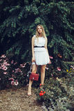 Beautiful blonde young adult woman wearing white dress and holding red bag posing in summer forest on flower meadow Stock Image