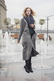 Beautiful blonde young caucasian woman in grey coat and scarf wa royalty free stock photo
