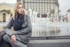 Beautiful blonde young caucasian woman in grey coat and scarf wa royalty free stock images