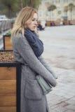 Beautiful blonde young caucasian woman in grey coat and scarf wa Stock Photos