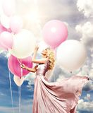 Beautiful girl with balloons. Beautiful blonde young cheerful woman in long pink dress holding many air balloons. collage with sky in background. copy space Stock Photos