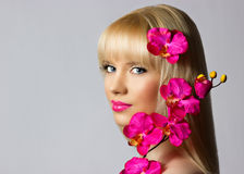 Beautiful blonde young girl with orchid flowers on grey background royalty free stock photos