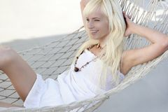 Beautiful blonde young girl relaxed on hammock. Profile stock image