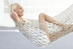 Beautiful blonde young girl relaxed on hammock. Profile royalty free stock photos