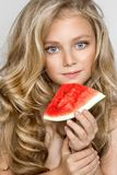 Beautiful blonde young model, cute girl, holding watermelon and looking cute. royalty free stock photo
