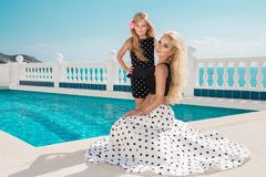 Beautiful blonde young mother and daughter, dressed in a polka dots dress. They stand on the amazing view of the sea in Santorini island royalty free stock image
