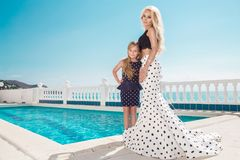 Beautiful blonde young mother and daughter, dressed in a polka dots dress. They stand on the amazing view of the sea in Santorini island stock images