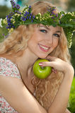 A beautiful blonde young woman. A beautiful blonde young woman with a wreath on his head eating Stock Photos