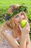 A beautiful blonde young woman. A beautiful blonde young woman with a wreath on his head eating Royalty Free Stock Photo