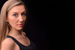 Beautiful blonde young woman in a black undershirt posing in a s Stock Image