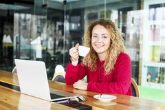 Beautiful blonde young woman drinking cappuccino coffee in a hipster bar and smiling. Curly haired female blogger, smiling, surfin royalty free stock photography