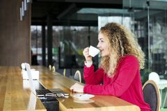 Beautiful blonde young woman drinking cappuccino coffee in a hipster bar and smiling. Curly haired female blogger, smiling, surfin royalty free stock image