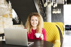 Beautiful blonde young woman drinking cappuccino coffee in a hipster bar and smiling. Curly haired female blogger, smiling, surfin stock image