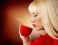 Beautiful blonde young woman drinking coffee Royalty Free Stock Photos