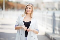 Beautiful blonde young woman on the embankment in the city royalty free stock photo
