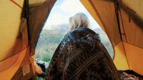 Beautiful blonde young woman enter in the tent camping just on big mountain. The concept of freedom in solitude among