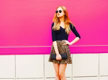 Beautiful blonde young woman in leopard skirt, sunglasses with handbag clutch posing on colorful pink. Wall background stock photos