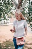 Beautiful blonde young woman with mobile phone on the street royalty free stock image