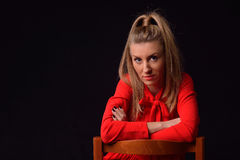 Beautiful blonde young woman in a red dress is sitting on a chai Stock Photography