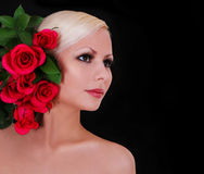 Beautiful blonde young woman with red roses over black Stock Image