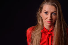 Beautiful blonde young woman in a red shirt posing in a studio o Royalty Free Stock Photos