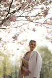Beautiful blonde young woman in Sakura Cherry Blossom park in Spring enjoying nature and free time during her traveling stock photography