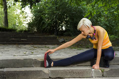 Beautiful blonde young woman stretching legs Stock Images