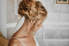 Beautiful blonde young woman with stylish wedding hairstyle in fashionable white lace lingerie posing at vintage. Interior stock photos