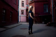 Beautiful blonde young woman walking on the street. Flare for text and design. Lifestyle girl in the city. Beautiful blonde young woman walking on the street Stock Photo