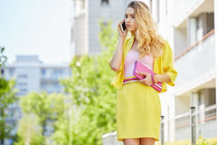 Beautiful blonde young woman walking on the street Stock Images