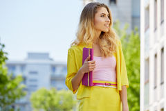 Beautiful blonde young woman walking on the street Royalty Free Stock Image