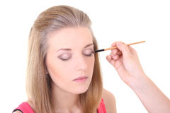 Beautiful blondie girl with make-up brush over white Stock Photo