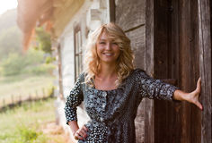 Beautiful blondie near country house in the sunset Stock Images