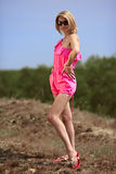 Beautiful blondie poses outdoors. Beautiful blondie in a pink beach costume posing on the dune in a national park Curonian Spit royalty free stock image