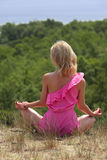 Beautiful blondie poses outdoors. Beautiful blondie sitting in the lotus position on a slope Royalty Free Stock Images