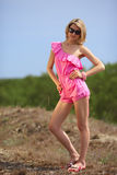 Beautiful blondie poses outdoors. Beautiful blondie in a pink beach costume posing on the dune in a national park Curonian Spit Royalty Free Stock Images