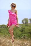 Beautiful blondie poses outdoors. Beautiful blondie in a pink beach costume posing on the dune in a national park Curonian Spit Stock Photo