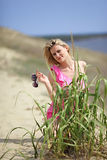 Beautiful blondie poses outdoors. Beautiful blondie in a pink beach costume posing on the dune in a national park Curonian Spit Stock Image