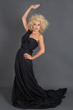 Beautiful blondie witch in long black dress posing Stock Photo