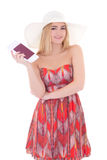 Beautiful blondie woman in red dress with passport and ticket is Stock Photos