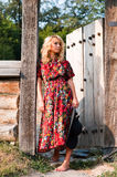 Beautiful blondie in the wooden gate Royalty Free Stock Photos
