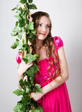 Beautiful blondy girl in red dress holding on to the green vine grapes Stock Images