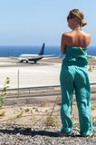 Beautiful blondy with long hair looking at airplane Royalty Free Stock Image