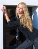 Beautiful blondy standing against windows Royalty Free Stock Photos