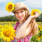 Beautiful Blondy Woman in Cowboy Hat with Sunflowers. Royalty Free Stock Photo