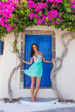 Beautiful blooming bougenvilia in old village Emporio on the island of Santorini in Greece. Beautiful girl in dress blooming bougenvilia with traditional old Stock Photography