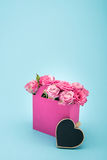 Beautiful blooming pink roses in decorative paper bag and blank heart symbol isolated on blue Stock Images