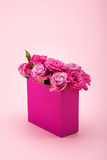 Beautiful blooming rose flowers in decorative paper bag arranged isolated on pink Stock Photo
