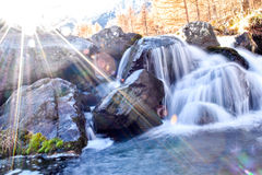 Beautiful blue Alpine waterfall in mountain forest with sun flare Royalty Free Stock Image