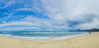 Beautiful blue beach panoramic sea view. Beautiful blue Beach Mallorca panoramic sea view on a windy day. Waves, sea, clouds, blue sky, concept of vacation Royalty Free Stock Images